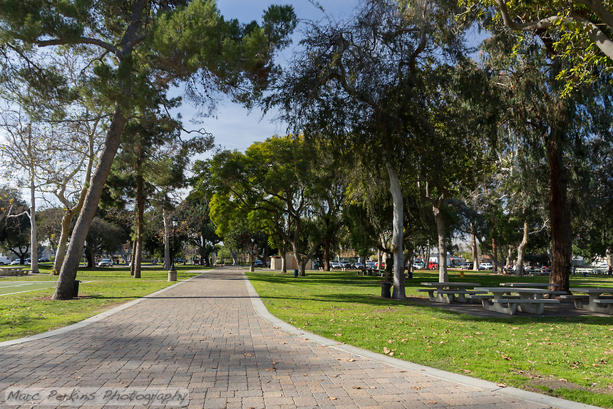 The grand paver pathway at South Gate Park leads through a wooded area with picnic tables.