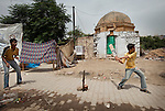 Children play street cricket outside their homes which are built into part of an ancient Lodhi Period tomb complex at Nizamuddin in Delhi, India. The Archaeological Survey of India has been on a campaign to evict people who have illegally made the tombs their homes throughout the city in recent times but is facing stiff opposition from the residents. The area is littered with tombs that need excavation.