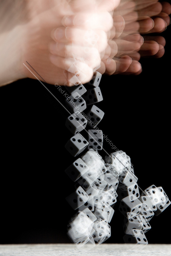 A stroboscopic image of a hand rolling a pair of dice.