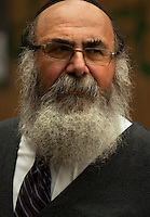 """Rabbi Yaakov Rapoport, Director of Chabad House Lubavitch at Syracuse University, stands on Marshall Street to wish students a happy Sukkot and perform mitzvahs on Hoshana Rabbah. Hoshana Rabbah is the seventh day of the Jewish holiday of Sukkot and is considered the final day of the divine """"judgment"""" in which the fate of the new year is determined.  Photo by James R. Evans ©"""