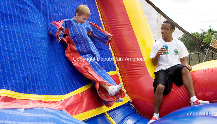 OXFORD CT. 08 June 2013-060813SV08-From left, Zachary Fleishman, 10, of Oxford hangs by a Velcro suit as Salim Lemond, 17, of Oxford watches during the fourth annual Oxford Day at Oxford High School in Oxford Saturday. The Oxford High School Booster Club hosted the event, which included games, entertainment, shopping and food. <br /> Steven Valenti Republican-American