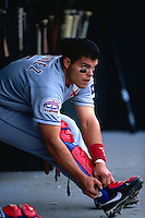 "SAN FRANCISCO, CA - Ivan ""Pudge"" Rodriguez of the Texas Rangers puts on his catcher's gear in the dugout during a game against the San Francisco Giants at Pacific Bell Park in San Francisco, California in 2000. Photo by Brad Mangin"