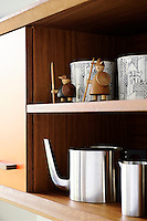 Items are displayed in on the shelf of stylish kitchen units handmade in water-resistant iroko with orange laminate on the door fronts and chamfered edges.