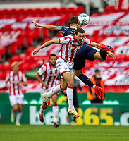 4th July 2020; Bet365 Stadium, Stoke, Staffordshire, England; English Championship Football, Stoke City versus Barnsley; Patrick Schmidt of Barnsley and James Chester of Stoke City jump for the ball