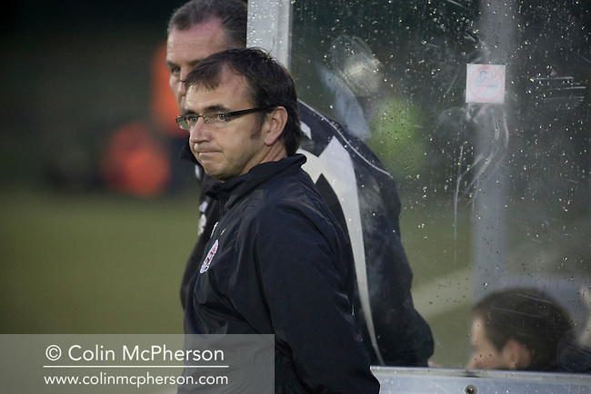 Pat Fenlon, manager of Irish club Bohemians watching the action through the rain at Park Hall Stadium, Oswestry during his team's Champions League 2nd qualifying round 2nd leg game away to The New Saints. Despite leading 1-0 from the first leg, the Dublin club went out following their 4-0 defeat by the Welsh champions. The match was the first-ever Champions League match in the UK played on an artificial pitch and was staged at the Welsh Premier League's ground which was located over the border in England.