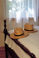 Still llife of two straw hats on the foot of a bed. Strasburg Pennsylvania USA Lancaster County.