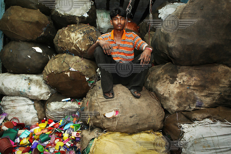 An employee at a small workshop sitting on sacks of used plastic. The plastic is sorted according to its colour, cut into tiny pieces and then sold on. The waste recycling industry is helping thousands of slum dwellers out of poverty. The recycling of the discarded waste of Mumbai's 19 million citizens is a thriving business propelled by thousands of micro entrepreneurs. Economists estimate that the output of the slum is over 1 billion USD a year.