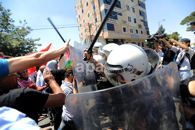 Palestinian riot police clash with protesters demonstrating against the upcoming negotiations between Palestinian leaders and Israel, a they try to march towards headquarters of Palestinian president Mahmud Abbas, in the West Bank city of Ramallah on July 28, 2013. Israeli Prime Minister Benjamin Netanyahu was seeking cabinet approval for a contentious release of 104 veteran Palestinian and Israeli-Arab prisoners, to coincide with the resumption of peace talks which have been stalled since September 2010. Photo by Issam Rimawi
