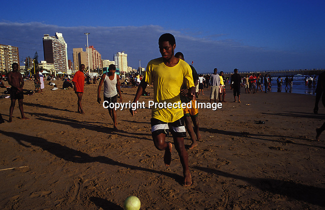 soccer,fotball,beach,men,sand,sunset,sport.Men plays soccer on the beach during a December holiday at Durban's north beach, in Natal, South Africa..©Per-Anders Pettersson/iAfrika Photos