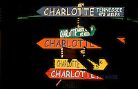 "Photo of the iconic Charlotte signs statue/public art located on The Green in Uptown Charlotte. The Green, actually the top level of an underground parking garage, is a tiered outdoor space with a lawn, lush gardens, interactive fountains and abundant public art. Contemporary artist Gary Sweeney, based in San Antonio, created the piece named ""Charlotte - The Center of the Known World."" The signs point to 11 other areas also named Charlotte. The signs point to the approximate direction of the locales they identify and the distance to each. .."