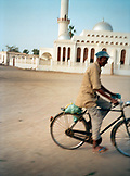 ERITREA, Massawa, a man rides his bicycle in front of a mosque in Massawa