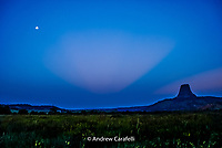The first rays of daylight break the horizon as the moon starts to set behind Devil's Tower, Wyoming.