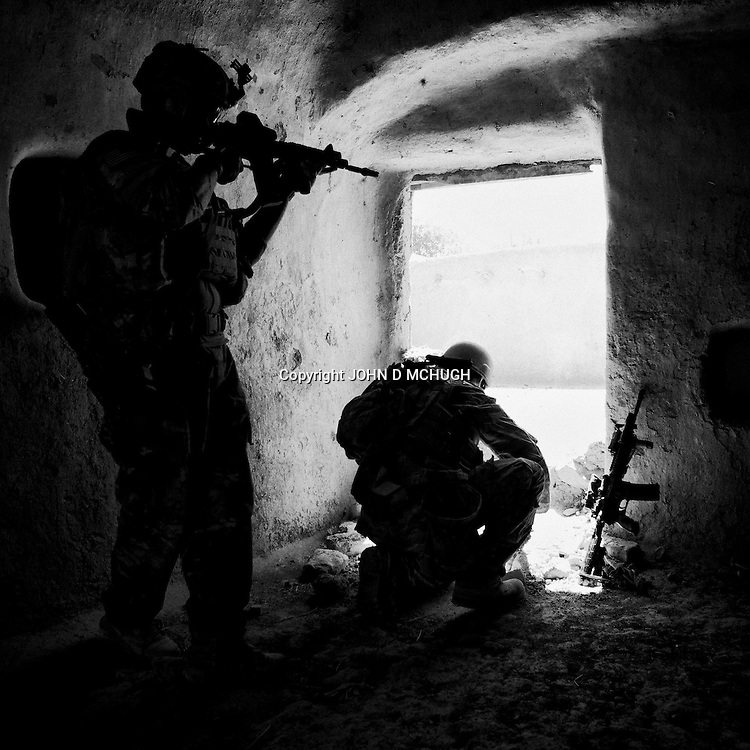 PFC Fulford (L), and 1LT Brien from 1 Platoon, Delta Co, 1-66, 4th Infantry Division, search for arms caches and IEDs around Jazah village in the  Arghandab Valley, Kandahar, 03 May 2011. (John D McHugh)