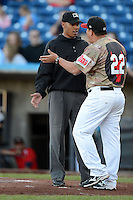 Quad Cities River Bandits manager Omar Lopez #22 argues a call with umpire Jeremie Rehak during a game against the Wisconsin Timber Rattlers on May 24, 2013 at Modern Woodmen Park in Davenport, Iowa.  Quad Cities defeated Wisconsin 4-3  (Mike Janes/Four Seam Images)