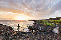 A woman and her dog pause to take in the sunset as they hike the historic 1871 Trail in Honanau, Big Island. The ancient trail was the main artery for coastal travel between several villages in the area.