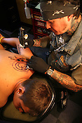 May 31, 2009. Raleigh, NC. .Ryan Alexander tattoos the band Blink 182's symbol on the left shoulder of Corey Ault at Blue Flame.