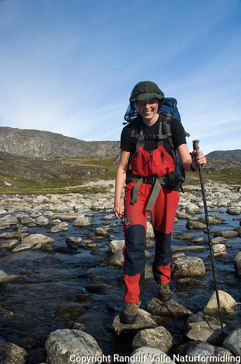 Jente med mygghatt, vandrestav og ryggsekk krysser grunn elv ---- Girl crossing shallow river