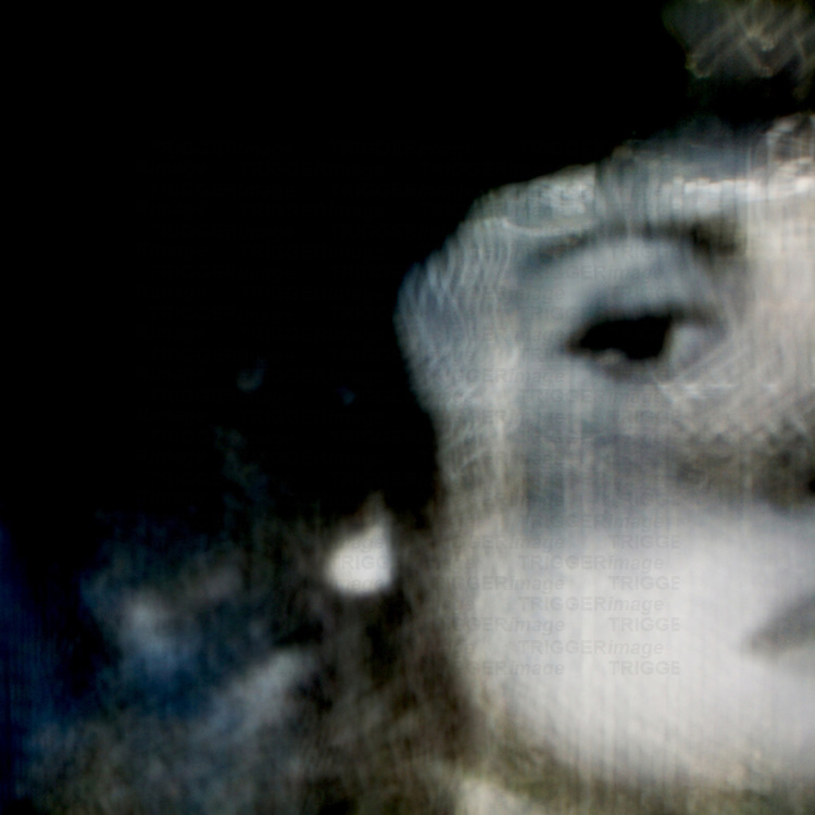 textured close up of of woman's face  half in shadows