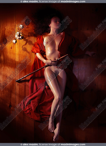 Beautiful nude woman with a bamboo flute in red kimono lying on the floor in dim dramatic light view from above