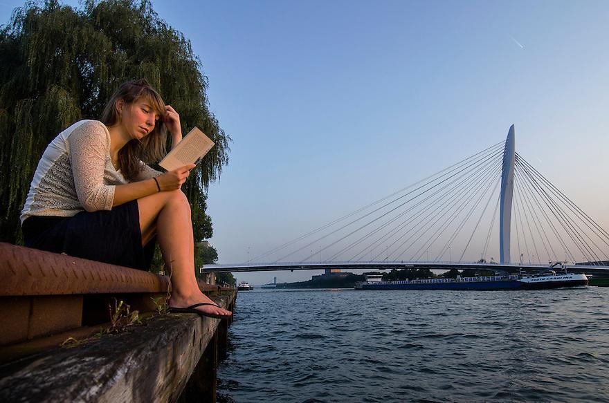 Nederland, Utrecht, 3 okt 2014<br /> Jonge vrouw leest op een zachte nazomeravond een boek aan de kade van het Amsterdam Rijnkanaal in Utrecht.  Foto: (c) Michiel Wijnbergh