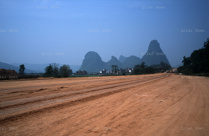 An unpaved highway still under construction cuts through the Karst mountains near Guilin, Guangxi Province, China on 19 October, 2008. China has undergone a major road building project as an investment in basic infrastructure and a cornerstone in economic development, linking cities by highways and vowing to extend its road network to every village in the country. More than 33,000 kilometers (20,500 miles) of highways have been built in the last five (5) years and China is on track to top the U.S. in terms of roadways...