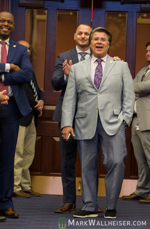 A Senate Sergeant of Arms taps Sen. Gary Farmer, Jr., center, D-Ft Lauderdale, on the shoulder as he is called out during Senate debate for wearing tennis shoes on the Senate floor as Sen. Randolph Bracy, left, looks on at the Florida Capitol in Tallahassee, Florida.
