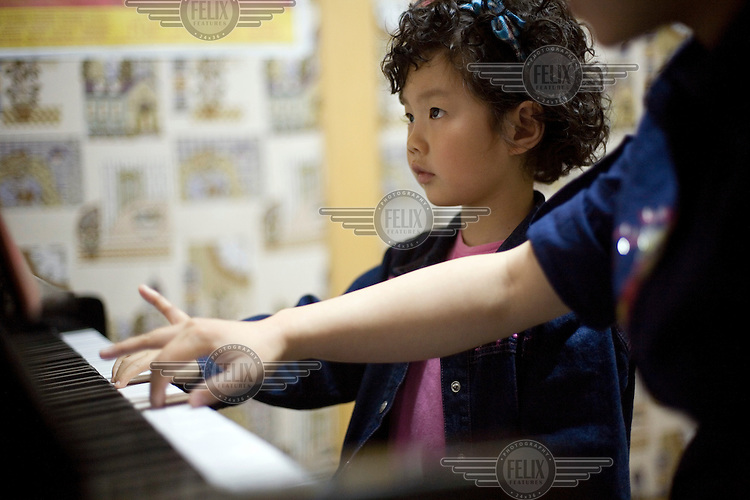 Four-year-old Su Jingnan during a piano lesson.
