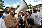 A woman plugs her ears as a man announces how villagers should line up for the distribution of food and other emergency supplies by the Lutheran World Federation, a member of the ACT Alliance, in the village of Gressier outside of Port-au-Prince, Haiti. A January 12 earthquake ravaged the Caribbean nation, leaving hundreds of thousands hungry and increasingly frustrated and desperate.