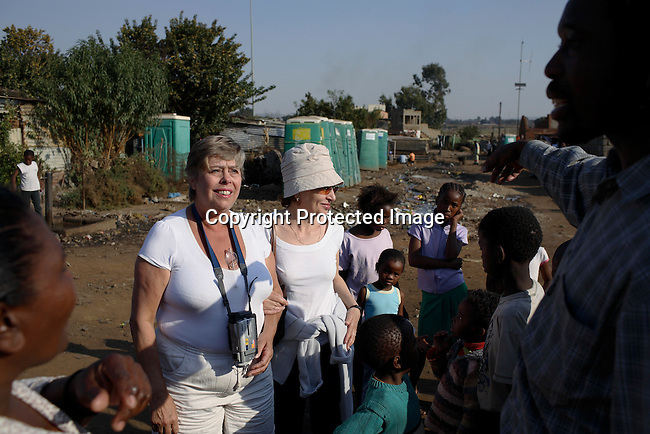 European tourists visits children at the Chris Hani squatter camp, one of the poorest areas in Soweto.