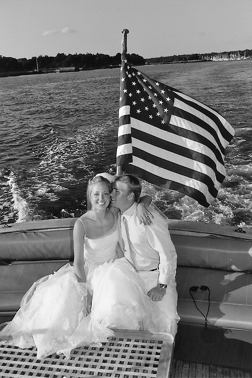 A bride and groom on a speedboat in Long Island Sound.