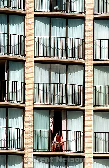 Shirtless man on a hotel balcony reading a book.<br />