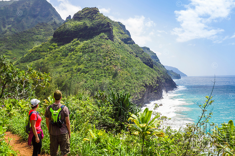 Two hikers admire the view along the Kalalau Trail near Hanakapi'ai Beach, Kaua'i.