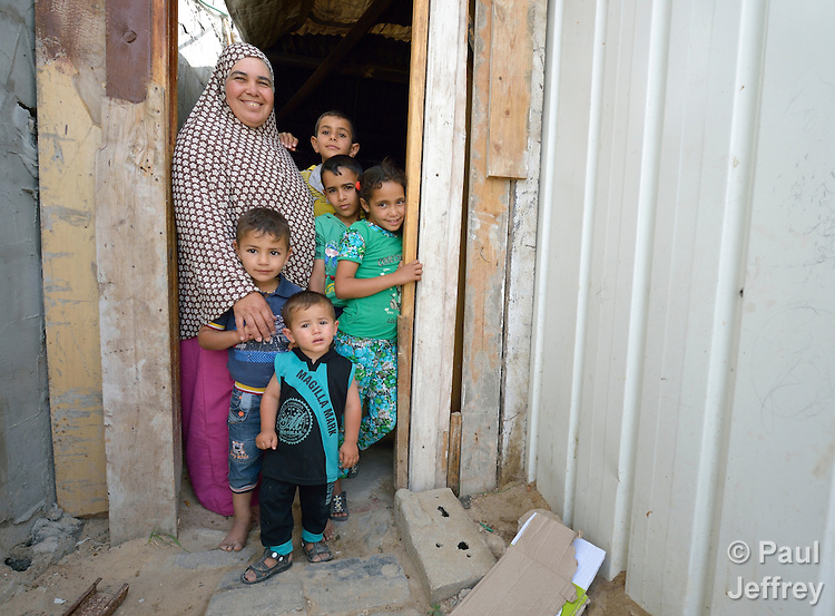 Fathiya Qasem and her family stand in the doorway of their transitional house in Beit Hanoun, Gaza. The house was provided by the local government after her home was destroyed by an Israeli air strike in 2014. The family received a water tank and hygiene supplies from International Orthodox Christian Charities, a member of the ACT Alliance. Before the water tank was installed, the children of the family had to walk 15 minutes to a United Nations school to carry back water. Now, according to their mother, they can spend their time studying.