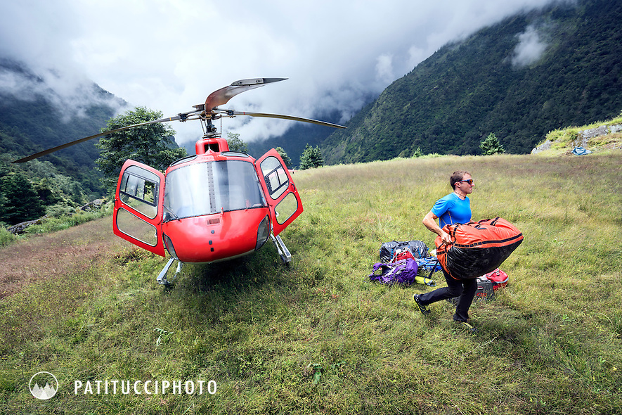 Ueli Steck carrying duffel bags from a helicopter after being flown into the Khumbu Valley