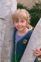 Girl age 7 playing around birch tree.  St Paul  Minnesota USA