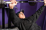 Education High School physical education male student working out on gym equipment