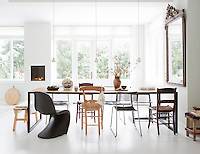 Light streams into the open plan dining area of the villa, which is then reflected around the pale green interior by the  varnished white wooden floor