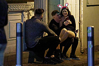 Pictured: Christmas revellers sit in a door frame in Wind Street, Swansea, Wales, UK. Friday 20 December 2019<br /> Re: Black Eye Friday (also known as Black Friday, Mad Friday, Frantic Friday) the last Friday before Christmas, in Swansea, Wales, UK.