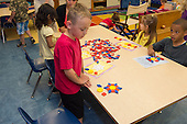 MR / Schenectady, NY. Zoller Elementary School (urban public school). Kindergarten inclusion classroom. Student (boy, 5) looks at pattern he created with pattern blocks by following directions on card during math learning center time. This activity helps develop visual recognition, shape awareness, and cognitive development skills. MR:Bur12. ID: AM-gKw. © Ellen B. Senisi.
