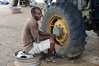 ZAMBIA, Mazabuka, Chikankata area, medium scale farmer Stephen Chinyama, homestead with John Deere tractor, pumping a flat tyre with small hand pump