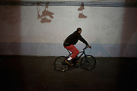 The shadow cast on a wall from sneakers dangling from electricity cables. Night bicycle rides,  Mexico City.