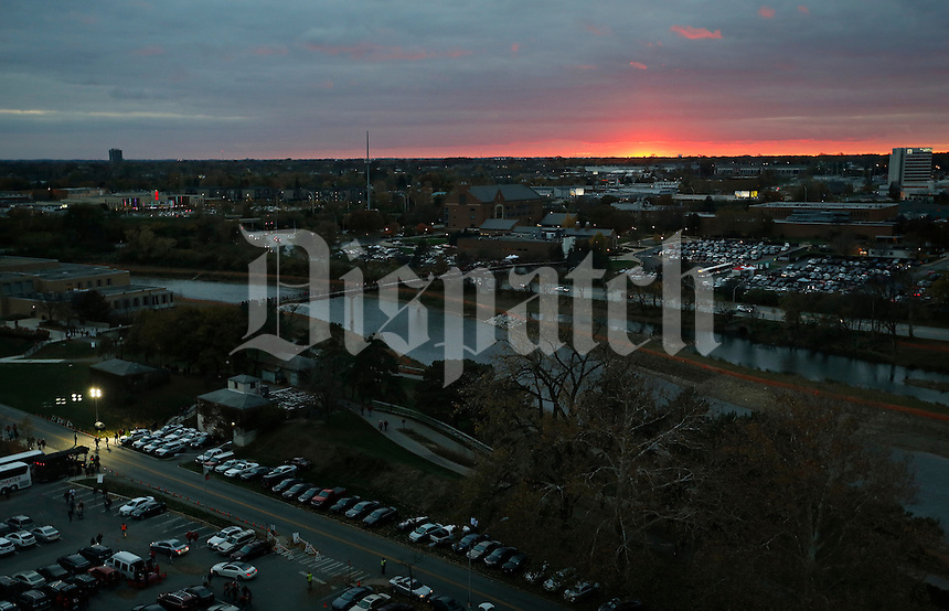 With the sun setting in the distance, fans stream across the Olentangy River for Ohio State's night game against Illinois at Ohio Stadium on Nov. 1, 2014. (Adam Cairns / The Columbus Dispatch)