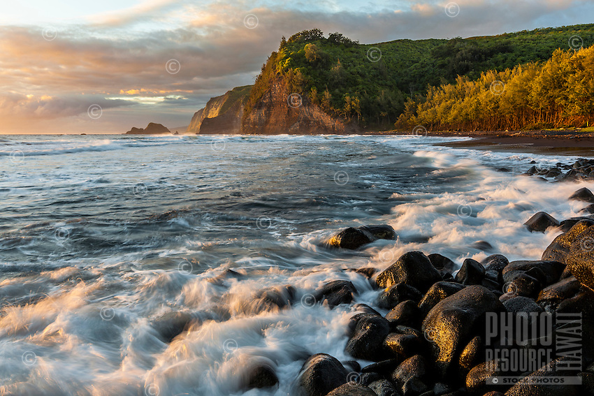 Light from the rising sun hits Pololu Valley's black sand beach and the rocks where the valley's river meets the ocean, North Kohala, Big Island.