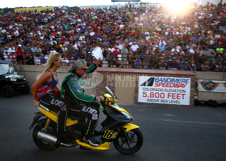 Jul. 18, 2014; Morrison, CO, USA; NHRA funny car driver John Force (right) waves his hat as he rides his scooter with daughter Courtney Force during qualifying for the Mile High Nationals at Bandimere Speedway. Mandatory Credit: Mark J. Rebilas-