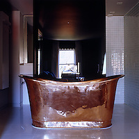 A free-standing copper bath dominates this tiled en-suite bathroom that is open to the bedroom beyond