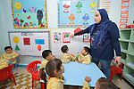 Maysaa Kanbour Nour helps children study in a school in the Sabra refugee camp in Beirut, Lebanon, run by the Department of Service for Palestinian Refugees of the Middle East Council of Churches. Most of the school's 148 students are Syrian refugees, but roughly one-third are Palestinian refugees and a few are poor children from the neighborhood. Lebanon hosts some 1.5 million refugees from Syria, and yet the government prohibits the establishment of large refugee camps, thus pushing many refugee families to search for housing in existing Palestinian refugee camps. This school is supported by the ACT Alliance.