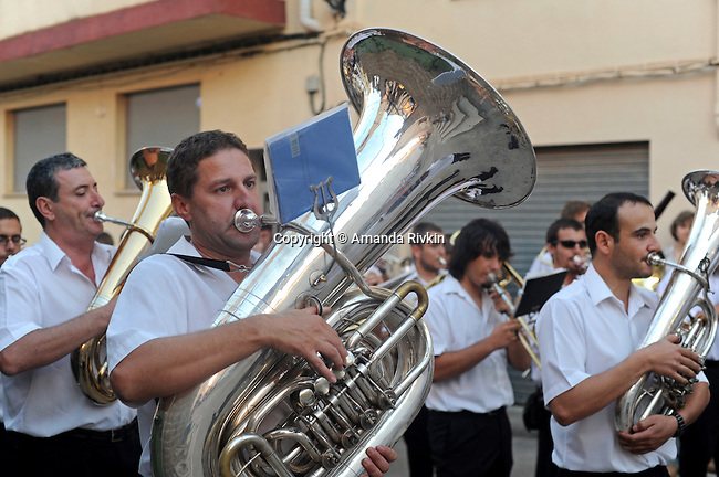 An orchestra parades through the square surrounding the church signaling the start of a procession towards the cavalry and cemetery during the municipal fiestas in Costur, Spain on August 16, 2009.