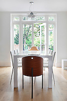 A minimalist white dining room with French doors leading to the garden. The room is sparsley furnished with a white table and chairs and two wooden chairs at either end.