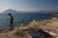 Grecia, Patrasso 2011. Rifugiati  accampati lungo la spiaggia. Un immigrato in pantaloncini e petto nudo sulla spiaggia. Vicino la struttura di una tenda e un sacco a pelo. Grece ville de Patras  2011 - refugies  dorment au bord de la plage