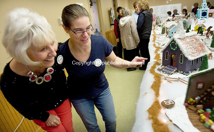 MIDDLEBURY CT. 05 December 2014-120614SV07-From left, Beverly Odonnell of Southington and Kristine Boisits of Middlebury check out Kristine&rsquo;s Church of New Life gingerbread church during the annual Gingerbread Village and Christmas Bazaar at St. George's Episcopal Church in Middlebury Saturday.<br /> Steven Valenti Republican-American